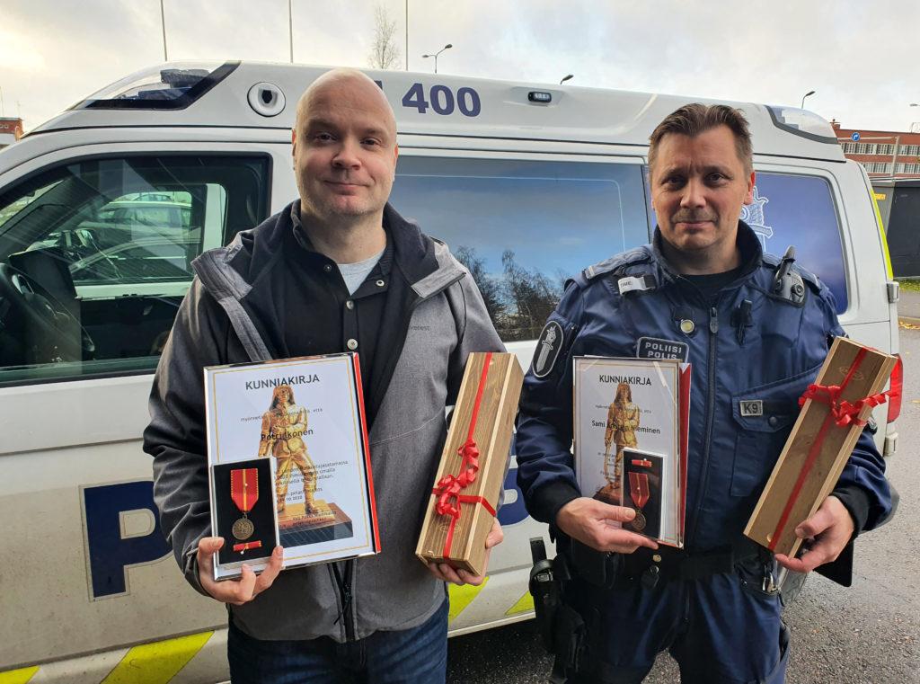 Palkitut poliisit kunniakirjat sekä Hämeen pelastusliiton mitalit kainalossa. Takana poliisiauto.