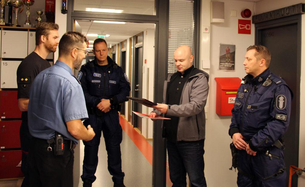 Pelastuspäällikkö Veli-Pekka Niemikallio ohjentaa kunniakirjan palkituille poliiseille.