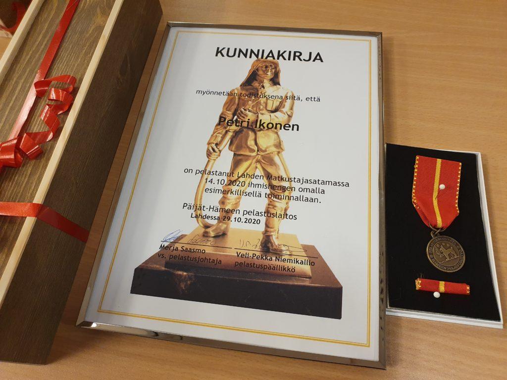 Kuva pelastuslaitoksen kunniakirjasta  sekä Pelastusliiton mitalista.