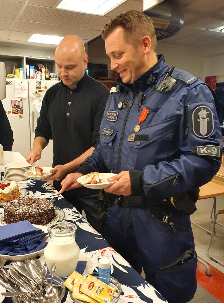 Palkitut poliisit leikkaavat täytekakkua.