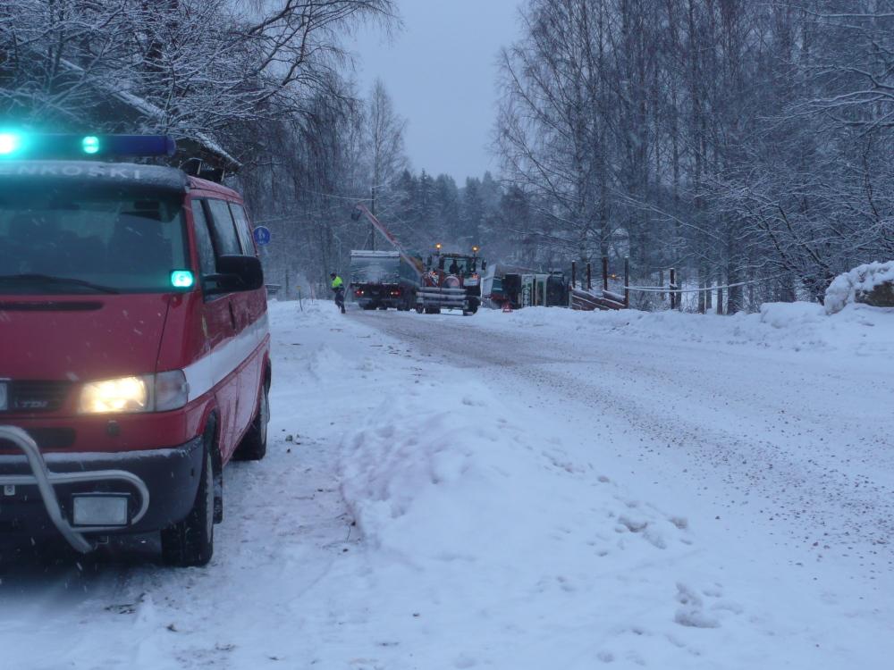 Rekka kaatunut lumisella tiellä. Traktori ja pelastusajoneuvoja apuna.