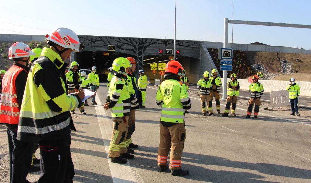 Palomiehiä kokoontuneena maantietunnelin eteen kypärät päässä ja keltaiset huomiovaatteet päällä.