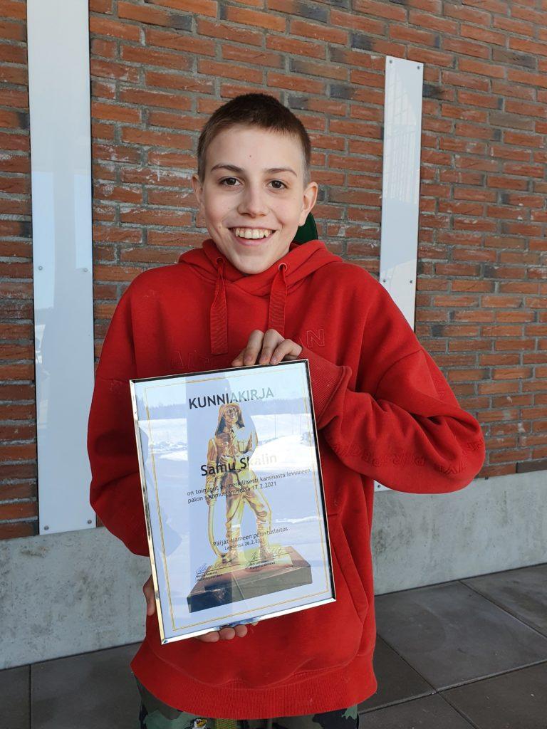 14-vuotias poika kunniakirja kädessä punaisessa hupparissa, iloinen ilme. Taustalla paloaseman tiiliseinä.