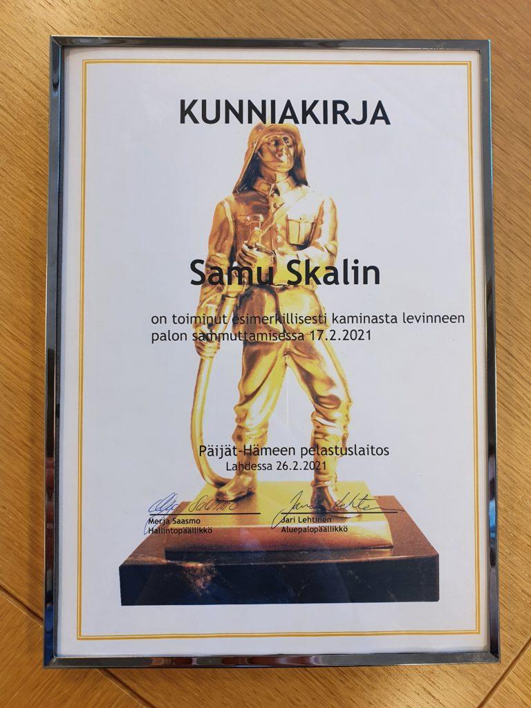 Kehystetty kunniakirja, jossa palomiespatsas ja teksti Samu Skalin on toiminut esimerkillisesti kamiinasta levinneen palon sammuttamisessa 17.2.2021. Päijät-Hämeen pelastuslaitos