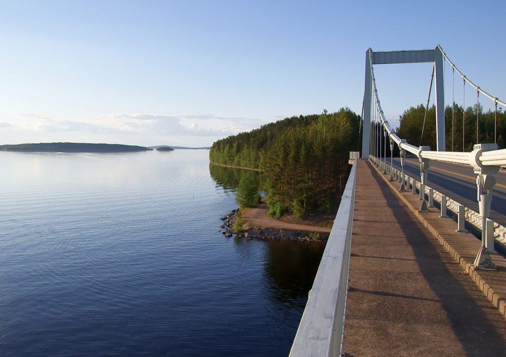 Maantiesilta auringonpaisteessa. Alla sininen järvi ja saaria, taustalla sininen taivas ja metsää.