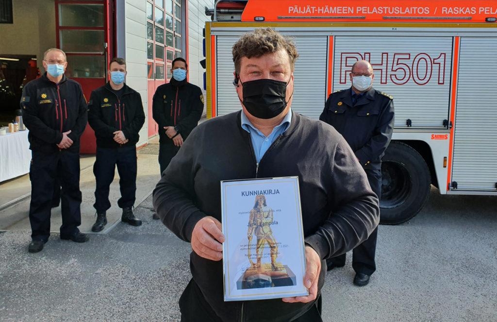 Palkittu Jyrki Lampola kunniakirja kädessään edessä. Takana paloauto, paloaseman tiloja ja pelastuslaitoksen henkilökuntaa sinisissä virkavaatteissa. Kaikilla kasvomaski.