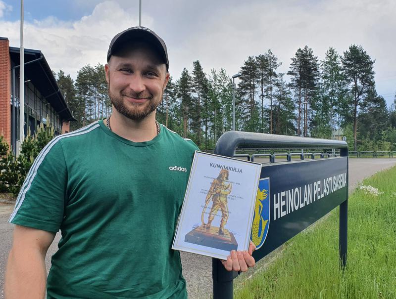 Hymyilevä Niko Nieminen kunniakirja kädessä Heiolan pelastusaseman edustalla. Vieressä aseman nimikyltti.
