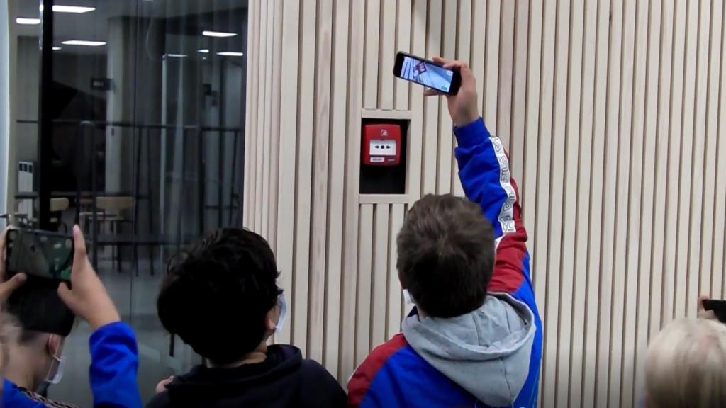 Poikia kuvaamassa puhelimilla palohälytyspainiketta seinässä.